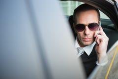 Biznesmen jest ubranym okulary przeciwsłonecznych na telefonie Obrazy Royalty Free
