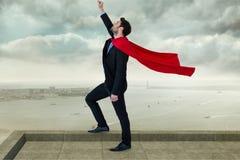Biznesmen jest ubranym przylądek z ręką podnoszącą podczas gdy stojący przeciw chmurnemu niebu fotografia royalty free