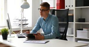 Biznesmen jest ubranym szkła, siedzący przy stołową i patrzeje kamerą zbiory wideo