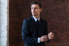 Biznesmen jest ubranym wristwatch stoi blisko biurowy nadokienny patrzeć daleko od Fotografia Royalty Free