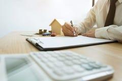 Biznesmen kalkuluje cena sprzedaży domowego biznes Agenta domowy ins obraz stock