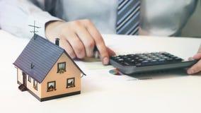 Biznesmen kalkuluje koszt budynku dom zbiory