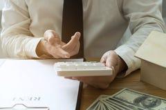 Biznesmen kalkuluje zakup - cena sprzedaży dom Faktorski sprzedaż dom zdjęcia stock