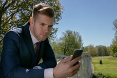 Biznesmen, kierownictwo w błękitnym kostiumu używać wiszącą ozdobę, telefon komórkowy w parku obraz royalty free