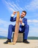 Biznesmen koncentrujący siedzi teczki niebieskiego nieba tło Biznesmena formalny kostium myśleć o biznesowym chwycie ośniedziałym fotografia royalty free