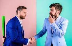 Biznesmen kryjówki uderzają za plecy podczas gdy trząść rękę Chowany zagrożenia pojęcie Partnerów biznesowych konkurenci biurowi zdjęcie stock