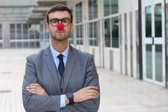 Biznesmen krzyżuje jego z czerwonym błazenu nosem ręki obrazy stock