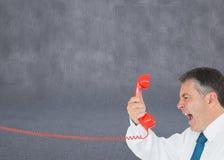 Biznesmen krzyczy bezpośrednio w handset Fotografia Stock