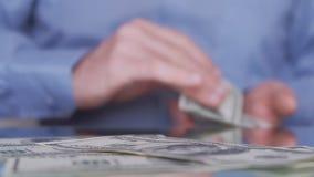 Biznesmen liczy dolarowych rachunki i bierze one od sto?u w zwolnionym tempie jeden po drugim zbiory