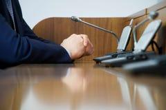 Biznesmen lub polityk w kostiumu siedzimy przed mikrofonem podczas gdy na obowiązku dyskutuje raport lub robi, fotografia stock