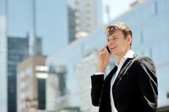 Biznesmen ma rozmowę telefonicza na smartphone na tło budynkach biurowych Zdjęcia Stock