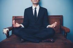 Biznesmen medytuje na kanapie Zdjęcie Stock