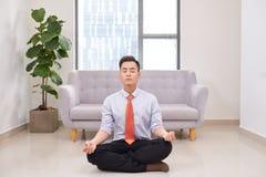 Biznesmen medytuje w lotosowej pozie na podłodze w biurze zdjęcie stock