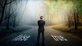 Biznesmen musi decydować który kierunek jest lepszy z słowa ` fałszywym ` i ` prawdziwy ` zdjęcie royalty free