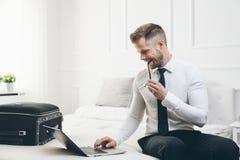 Biznesmen na łóżkowym działaniu z laptopem od jego pokoju hotelowego Zdjęcie Stock