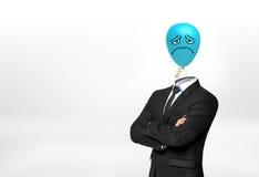 Biznesmen na białych tło stojakach z krzyżować rękami i błękitnym smutnym twarz balonem zamiast jego głowy Obraz Stock