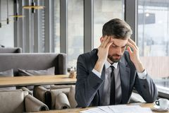 Biznesmen na biznesowym lunchu przy restauracyjny siedzący pobliski nadokienny mienie głowy czuć cierpiący zdjęcie royalty free