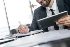 Biznesmen na biznesowym lunchu przy restauracyjnym obsiadaniem bierze notatki w organizatorze trzyma cyfrową pastylkę radosna zdjęcia royalty free
