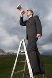 Biznesmen Na Drabinowym Używa megafonie W polu zdjęcie royalty free