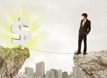 Biznesmen na rockowej górze z dolarową oceną Obraz Stock