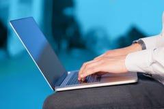 Biznesmen naciska nowożytnego laptop na kolorowym backgrou Zdjęcia Royalty Free