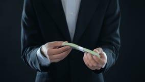 Biznesmen odbiorcza dolarowa zapłata i chować w kieszeni, wysoka pensja, premia zdjęcie wideo