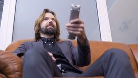 Biznesmen ogląda tv i zmiana kanały z pilot do tv zbiory wideo