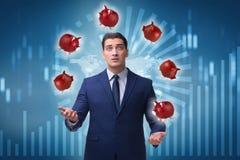 Biznesmen żongluje z piggybanks w biznesowym pojęciu Zdjęcia Royalty Free