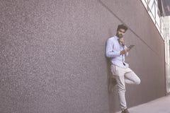 Biznesmen opiera na ścianie i trzyma ipod Przestrzeń dla obrazy royalty free
