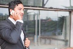 Biznesmen opowiada na mądrze telefonie w kostiumu podczas gdy stojący outsid fotografia royalty free