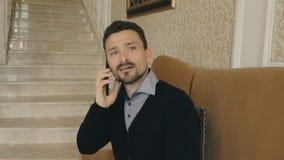 Biznesmen opowiada na telefonie i macha jego rękę zbiory