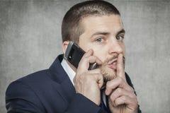 Biznesmen opowiada na telefonie i pyta dla ciszy fotografia stock