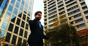 Biznesmen opowiada na telefonie komórkowym i trzyma cyfrową pastylkę zdjęcie wideo