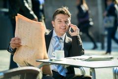 Biznesmen opowiada na telefonie komórkowym na ulica barze ma śniadaniową kawową czytelniczą gazetową wiadomość Zdjęcia Stock