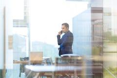 Biznesmen opowiada na telefonie komórkowym podczas gdy patrzejący przez biurowego okno Obrazy Stock