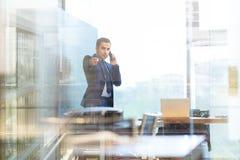 Biznesmen opowiada na telefonie komórkowym w korporacyjnym biurze, wskazuje kamera Fotografia Stock