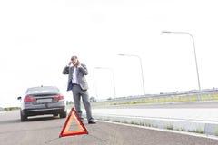 Biznesmen opowiada na telefonie podczas gdy stojący z awaria samochodem znakiem ostrzegawczym na drodze fotografia stock
