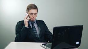 Biznesmen opowiada na telefonie przed laptopem w biurze w kostiumu zbiory wideo