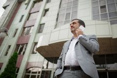 Biznesmen opowiada na telefonie na zamazanym budynku biurowego tle Przedsiębiorcy zawodu pojęcie kosmos kopii Obraz Royalty Free