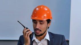 Biznesmen opowiada przy radia ustalonym obsiadaniem w biurze w hełmie Fotografia Royalty Free