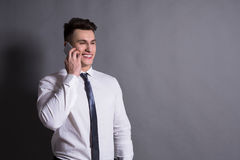 Biznesmen opowiada telefonem, przy szarym pracownianym tłem, kopii przestrzeń Obraz Stock