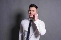 Biznesmen opowiada telefonem, przy szarym pracownianym tłem, kopii przestrzeń Zdjęcie Royalty Free