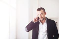 Biznesmen opowiada telefonem, stoi blisko okno Obrazy Royalty Free