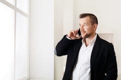 Biznesmen opowiada telefonem, stoi blisko okno Zdjęcie Royalty Free