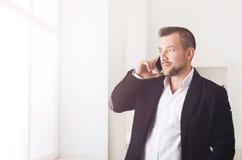 Biznesmen opowiada telefonem, stoi blisko okno Fotografia Stock