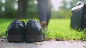 Biznesmen opuszcza jego buty teczkę i, chodzić bosy w zieleń parku zbiory