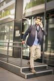 Biznesmen opuszcza pracę Biznesowy mężczyzna opowiada na mądrze telefonie obraz stock