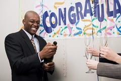 Biznesmen otwiera butelkę szampan Fotografia Stock