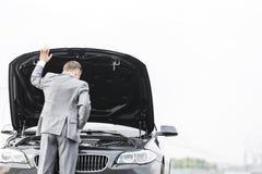 Biznesmen patrzeje awaria samochód przeciw niebu fotografia royalty free