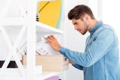Biznesmen patrzeje dla dokumentów w biurowej półce Obraz Stock